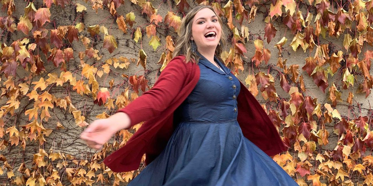 Becca dances out in the leaves in a dress